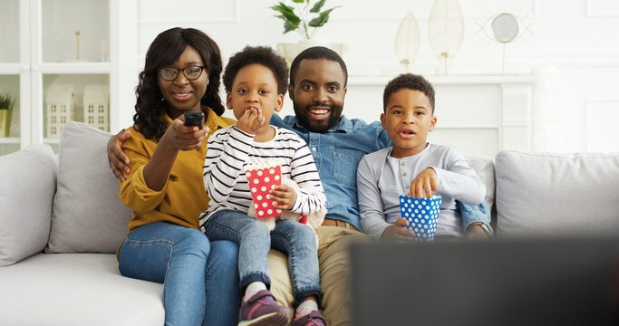 African american parents with little kids watching funny movies or tv show, eating popcorn, resting on sofa at home.