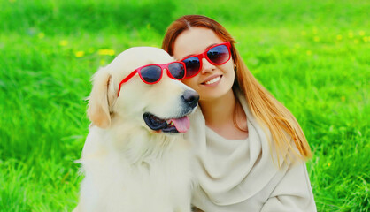 Portrait girl with her Golden Retriever dog wearing a sunglasses on green grass in the park