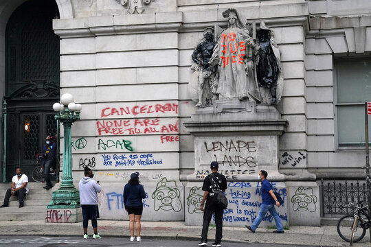 """People look at a wall of graffiti across from a protest to defund the police in a place they are calling the """"City Hall Autonomous Zone"""" in support of """"Black Lives Matter"""" in the Manhattan borough of New York City"""