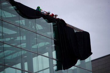 Greenpeace activists unroll a black fabric from the roof of the headquarters of the party Christian Democratic Union (CDU) in Berlin