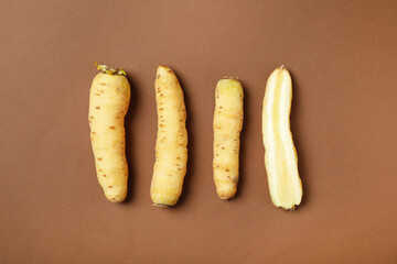 Fototapete - Whole and cut raw white carrots on brown background, flat lay