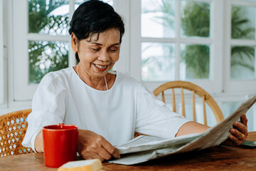 Happy senior Asian female in casual clothes reading interesting article in newspaper while having...