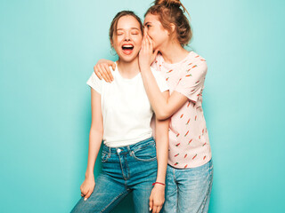 Two young beautiful blond smiling hipster girls in trendy summer hipster jeans clothes. Sexy...