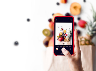 Closeup of woman taking picture with phone of fruits and berries in paper shopping bag over white background
