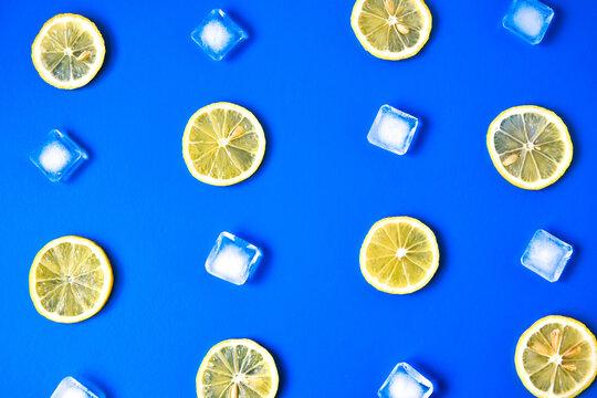 Lemonade layout with juicy lemon slices, ice cubes on blue background