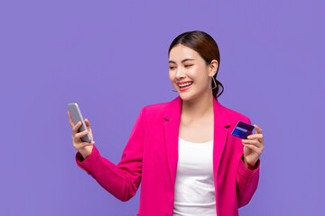 Happy beautiful young Asian woman in pink blazer shopping with credit card via mobile phone...