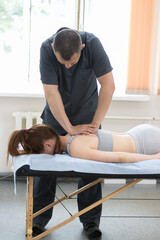 Young woman having osteopathy treatment - the master pushing on the back