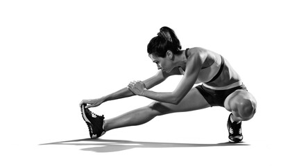 Sports. Woman at the gym doing stretching exercises and smiling on the floor