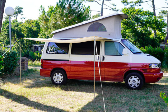 Camper Van Bulli westfalia red and white with roof up parked in camping area