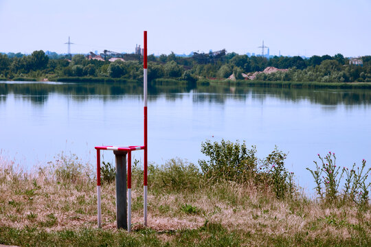 Well with a measuring bar for monitoring the groundwater level and water quality next to a gravel pond
