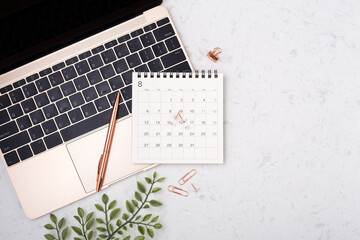 Calendar with rose gold pen on laptop