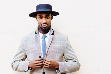 outdoor portrait of a black man looking to the camera while buttoning his suit