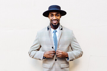 outdoor portrait of a black hipster man looking at camera smiling while buttoning his suit