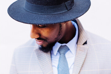closeup portrait of a hipster black man wearing a hat and looking to camera left with his eyes closed