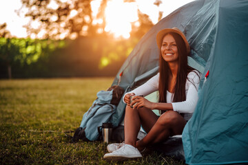 Portrait of a positive young woman sitting in tent, relaxing, copy space.
