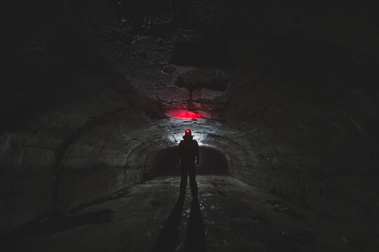 Dark silhouette of a researcher with a red lantern in the haulage tunnel in an abandoned mine. Spelestology.
