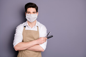 Portrait of his he attractive guy skilled virile muscular barber wearing safety mask holding in hands scissors comb social distance mers cov preventive measures isolated grey color background