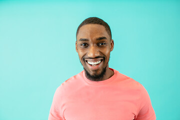 Portrait of a smiling happy African American man in peach color shirt looking at camera, with blue copy space around him