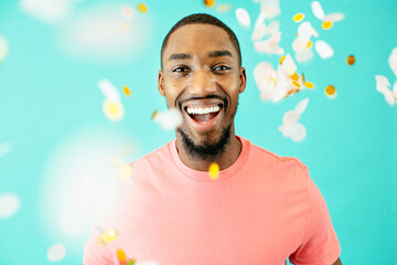 Portrait of a cheerful black man laughing looking at camera with confetti falling around