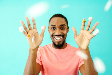 Close up portrait of a cheerful black man smiling looking at camera with his hands up and trowing confetti