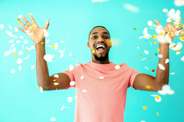 Portrait of a cheerful black man smiling looking at camera with his hands up and trowing confetti