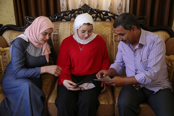Rama Abu Hashish, 17-years-old, who lost her arm in a car accident as a child, watches her pictures when she was a child with her parents at their home in Madaba