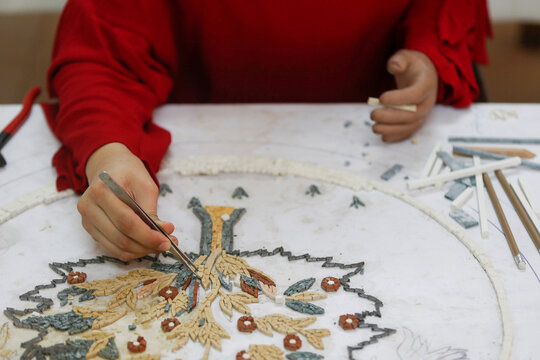 Rama Abu Hashish, 17-years-old, who lost her arm in a car accident as a child, working on a mosaic piece in a youth centre near her home in Madaba