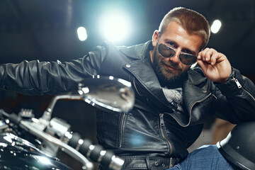 Portrait of bearded man motocyclist in dark sunglasses on dark background