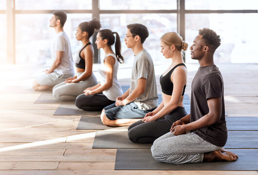 Wellness Concept. Young sporty people in yoga class making meditation exercises together