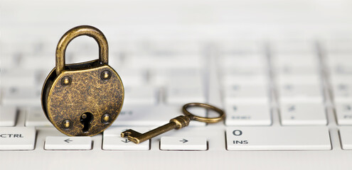 Internet online privacy, web security concept, padlock and gold key on a white computer laptop keyboard. Web banner.