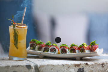 Sushi plate on the stone table with cocktail.
