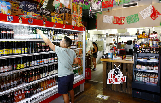 An employee places bottles on a refrigerated shelf at the La Taqueria, a Mexican restaurant in Zurich