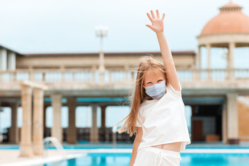 A cute kid in a medical protective mask, joyfully raised her hand up. Outdoor. Concept of...