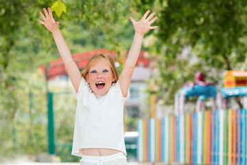 Emotions and expressions. The happy little girl raised her hands in the air. In the background, a...