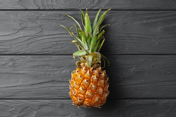 Ripe pineapple flat lay on black wooden background