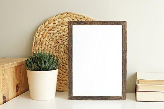 Boho style vertical empty photo frame, dark wood frame mockup, wooden sign mock-up for portrait artwork, bohemian interior, books, plant on white shelf.