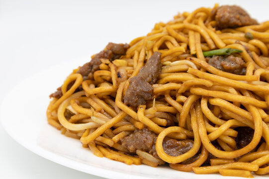 A Closeup of Beef Lo Mein Noodles on a White Plate with a White Background