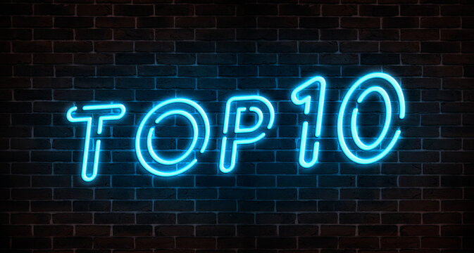Top 10 neon light text on empty red brick wall banner. Bright neon sign of top ten list winners at night. Design template of modern signboard or advertising.