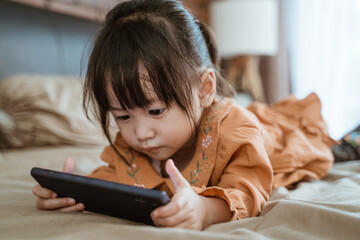 little girl laughed happily when holding a phone to see the child's video