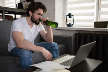 Man drinking beer and searching for job in internet
