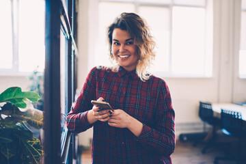 Half-length portrait of smiling female student using smartphone for sending chatting in social...