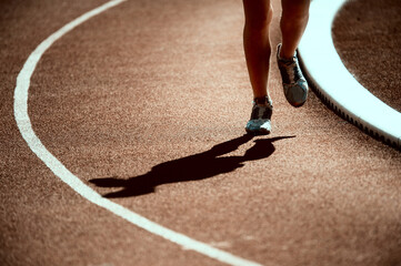 Shadow of a runner on the track.  Sports and healthy lifestyle concept.