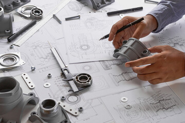 Engineer technician designing drawings mechanicalparts engineering Engine.manufacturing factory Industry Industrial work project blueprints measuring bearings caliper tools