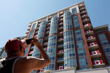A man photographs the Pearl and Pine Retirement Residence adorned with Canadian flags on Canada Day in Burlington