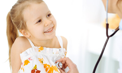 Doctor examining a child by stethoscope in sunny clinic. Happy smiling girl patient dressed in bright color dress is at usual medical inspection
