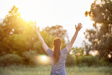 Woman athlete with hands up on the background of a sunny . Fotomurales