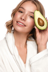 Beautiful tender young girl in a white coat with clean fresh skin posing in front of the camera with avocado in her hands. Beauty face. Skin care.