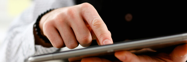 Male arm point finger using tablet pc display closeup. Stock market student management time chat...