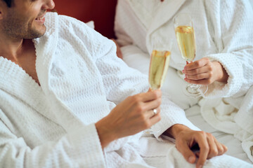 Close-up of a couple in bathrobes toasting with Champagne.