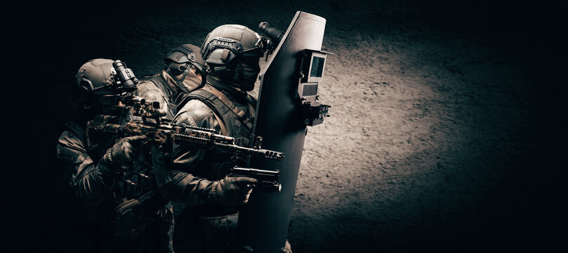 Image of three soldiers in a shooting computer game. ESports concept. They hide behind a tactical bulletproof shield.
